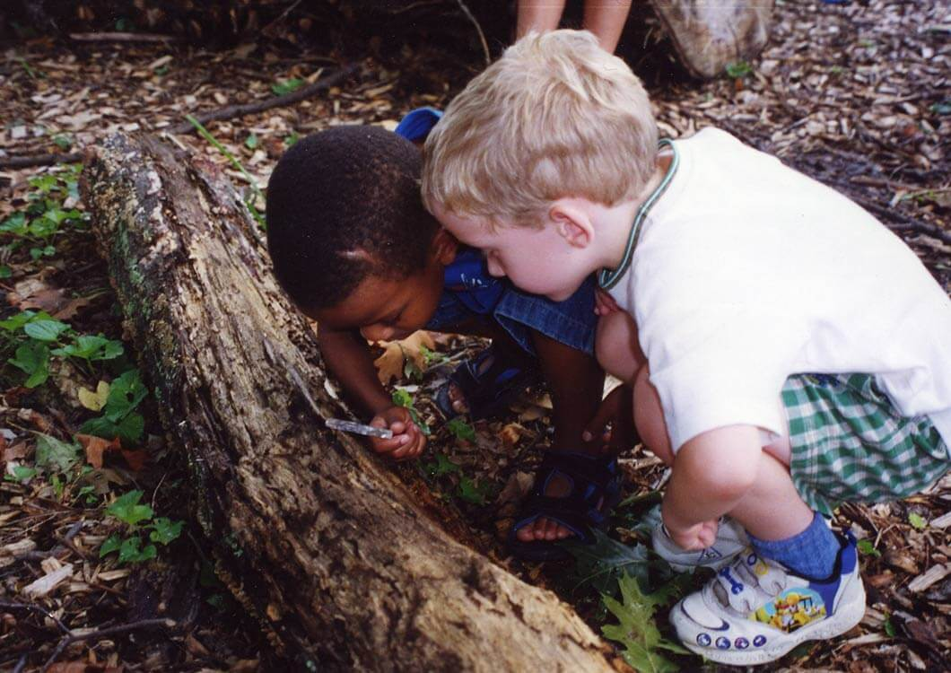Two young boys using a magnifying glass outside